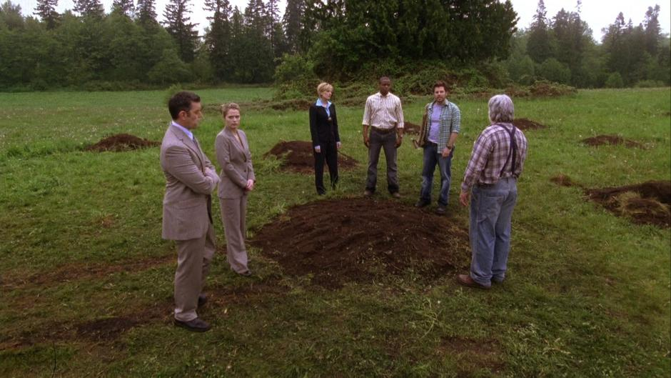 Lassiter, Juliet, Vick, Gus, and Walker stand around one of the holes while Shawn explains the case.