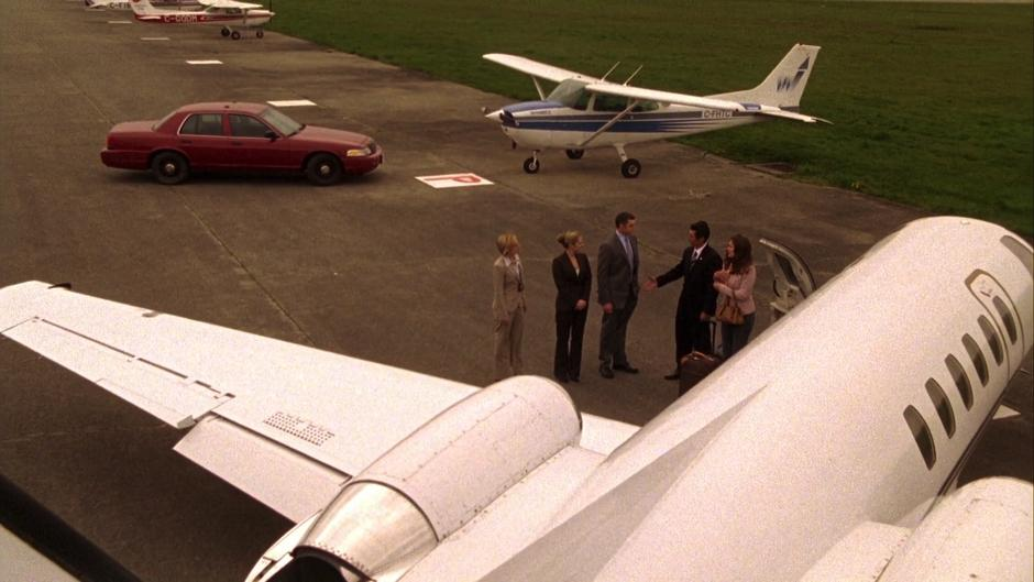 Ewing and Leikin say goodbye to Vick, Juliet, and Lassiter beside their private plane.