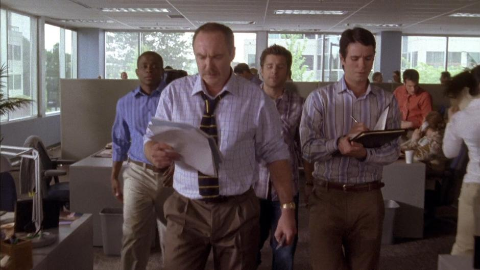 Gus and Shawn follow the paper's editor and his assistant through the office.