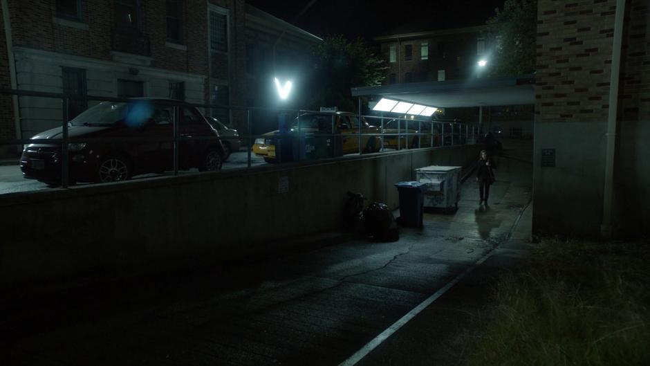 Quentin walks through the alley past some dumpsters.