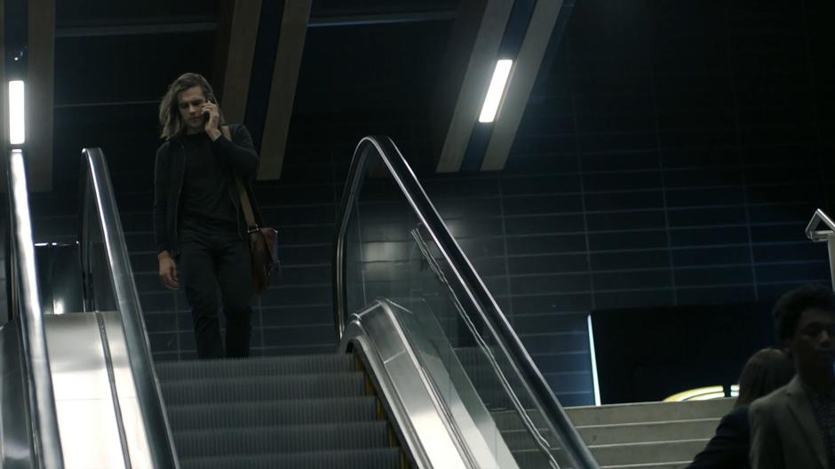 Quintin talks to Julia on the phone while he walks onto the top of the escalator.