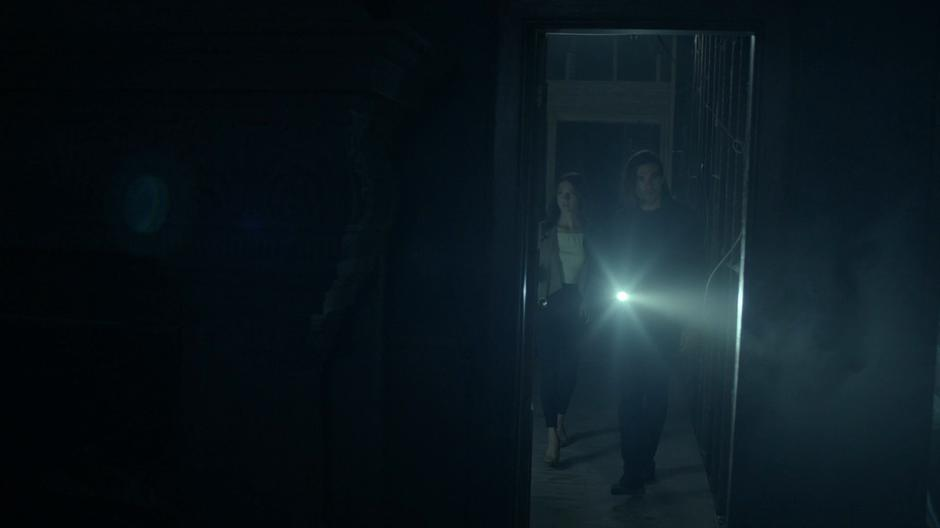 Julia and Quentin walk in through the entrance hallway into a darkened room.