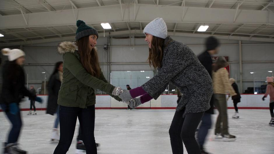 Ruby and Sam hold hands in the middle of the rink while preparing to race.