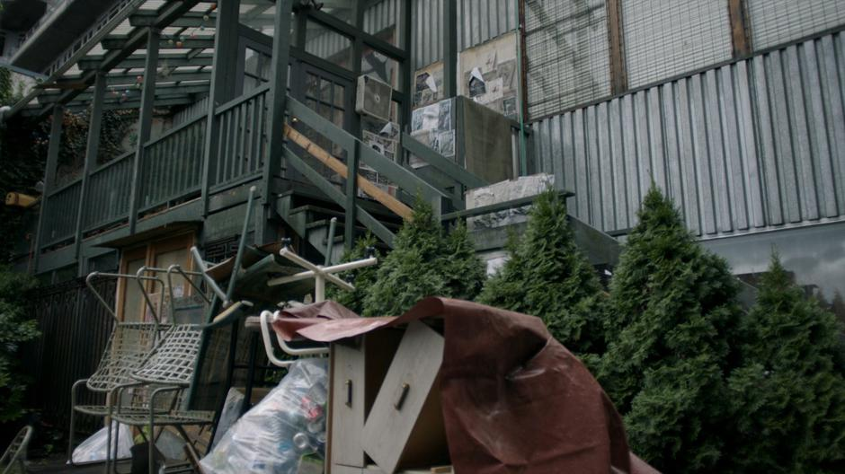 Establishing shot outside Reynard's apartment covered in junk.