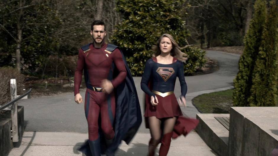 Kara and some dude jog into the edge of town.