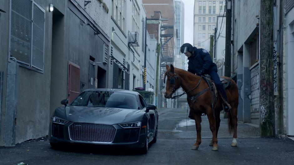 A police officer on horseback leans down to tell Blaine that he cannot park his car in the alley.