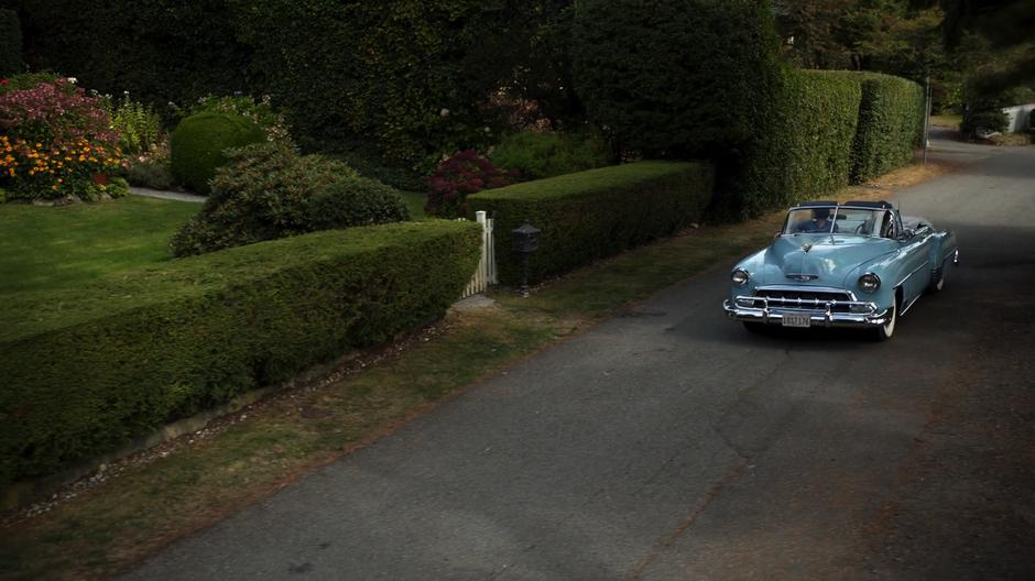 Kara drives Alex down the road near their childhood home.