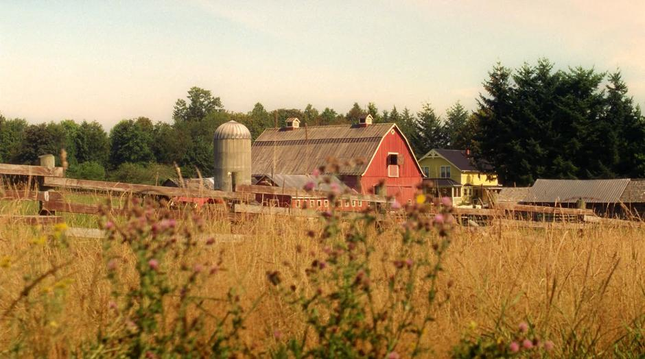 Establishing shot of the farm across a field.