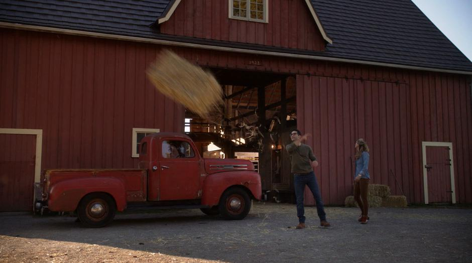 Clark throws a bail of hay while talking to Kara.