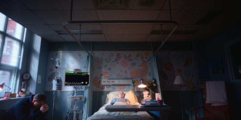 Director Stevenson sits praying beside his daughter's hospital bed.