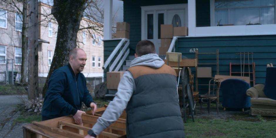 Gary and Trevor carry a dresser to the lawn in front of the house.