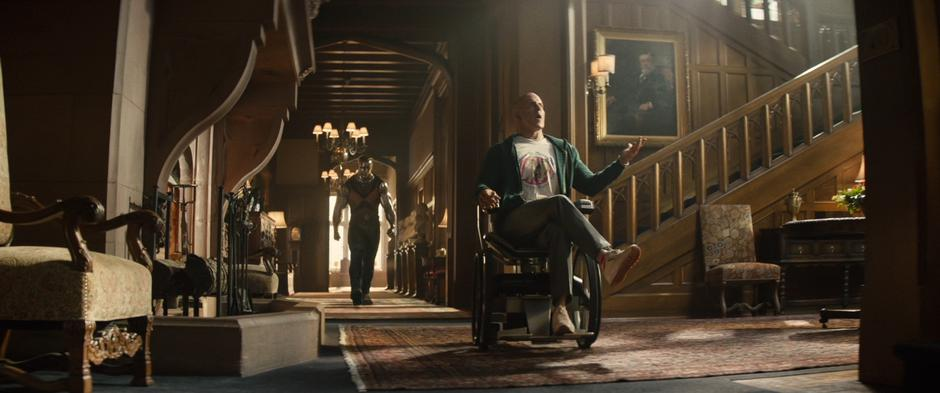 Colossus follows Wade as he rolls into the lobby on Xavier's wheelchair.
