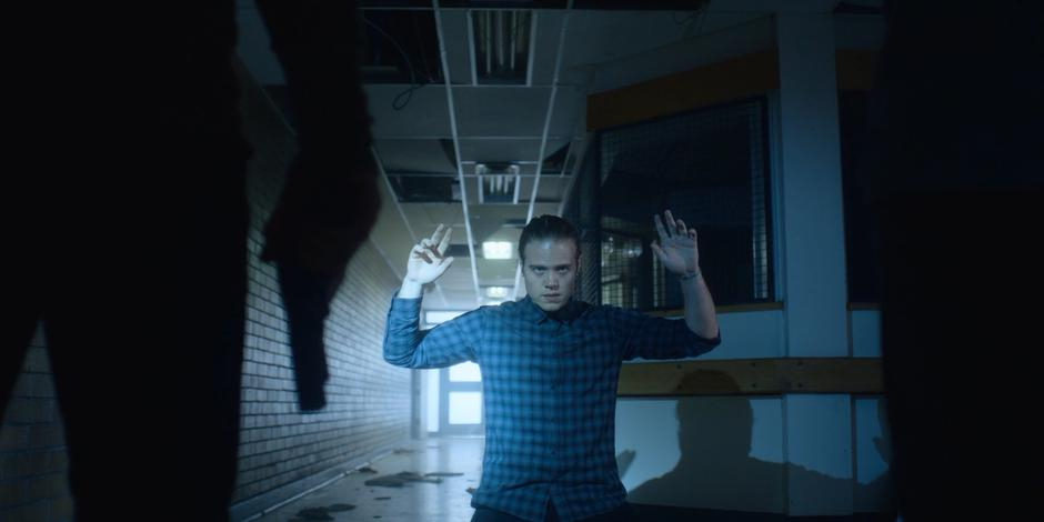 Philip kneels down in the hallway and puts his hands up.