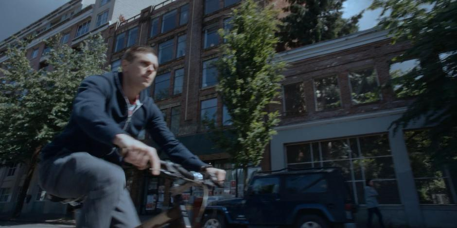 Trevor rides his bike down the street while telling Philip that he is on his way.