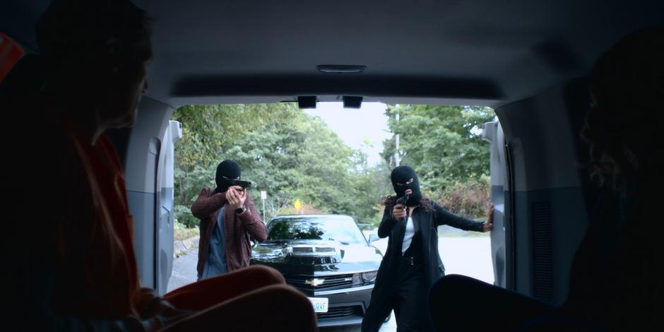 Trevor and Carly open the back of the police van wearing ski masks and holding guns to take Andrew Graham from Joanne.