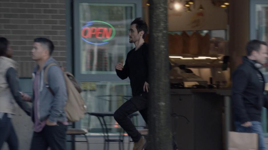 Mark runs down the sidewalk past several pedestrians.