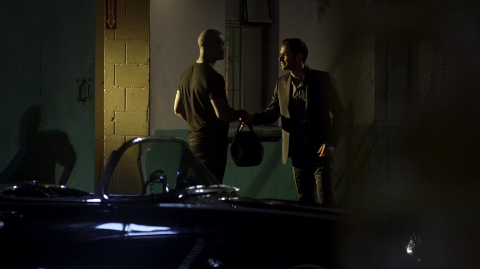 Lucifer exchanges a duffel bag with a guy behind a building at night.
