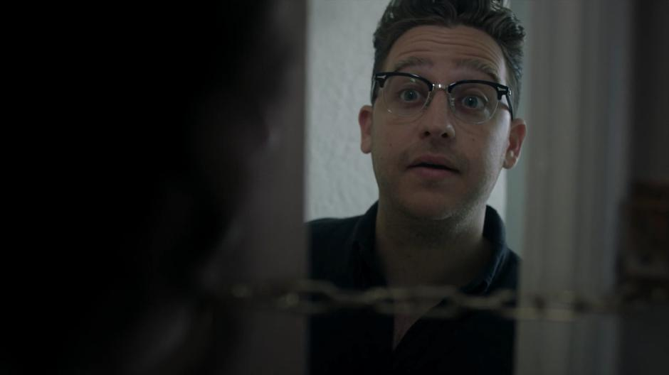 Josh talks to Enid through the chained door.