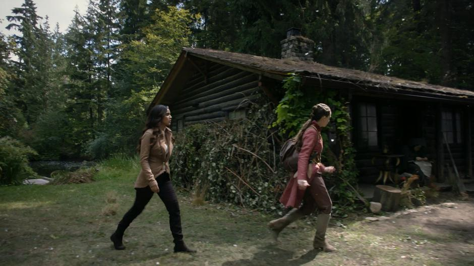 Margo and Fen walk around the side of the cabin to where a figure in a green cloak is sitting.