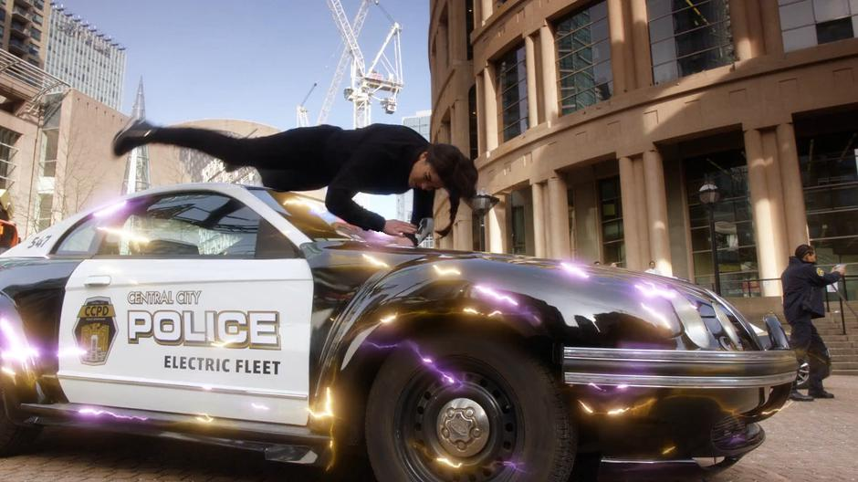 Nora flies over a parked police car which sparks with her electricity.
