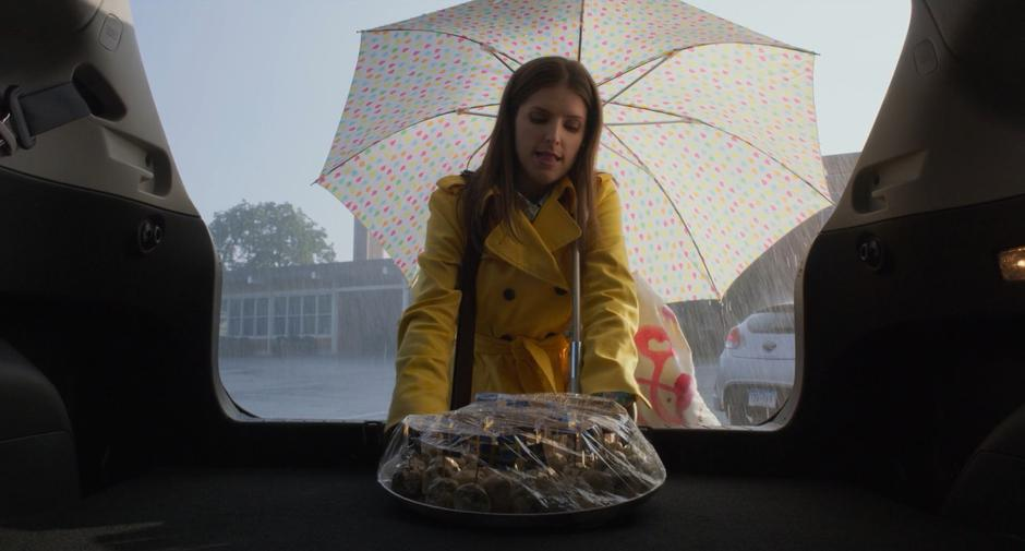 Stephanie takes a plate of snacks from her trunk in the rain.
