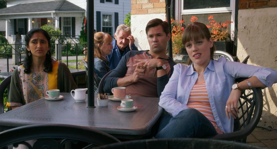 Sona, Darren, and Stacy sit with their coffee watching Stephanie across the street.