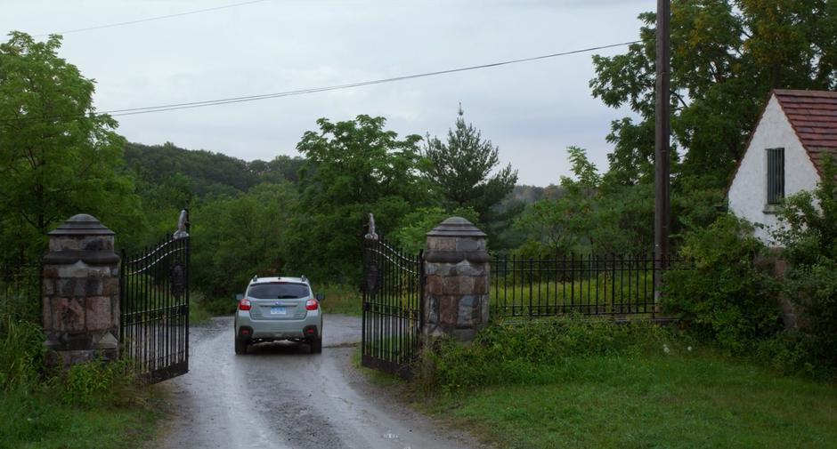 Stephanie drives through the gate though the woods towards the house.