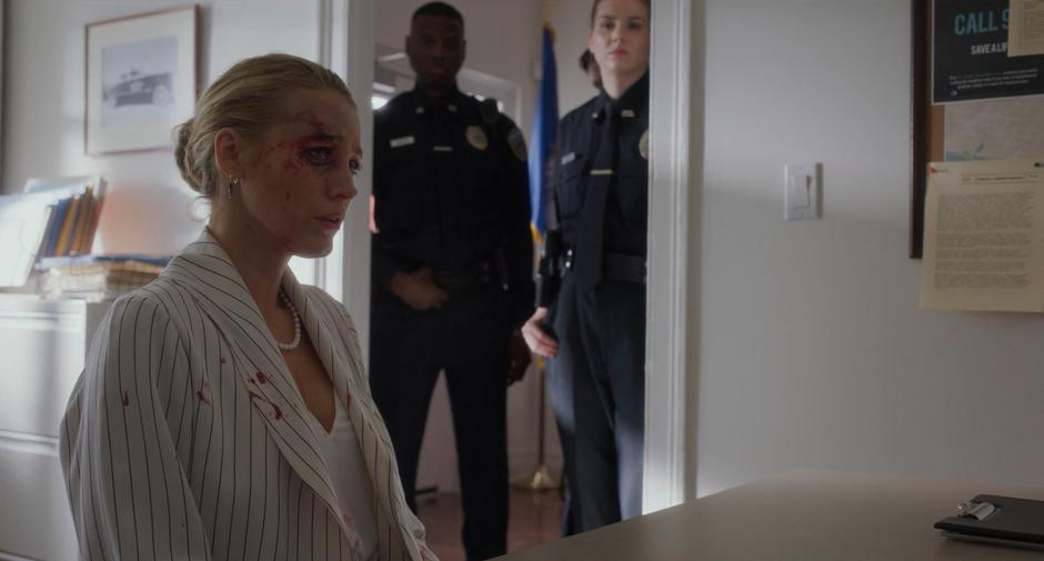 Two police officers watch from behind while Emily tells her cover story to the detective.