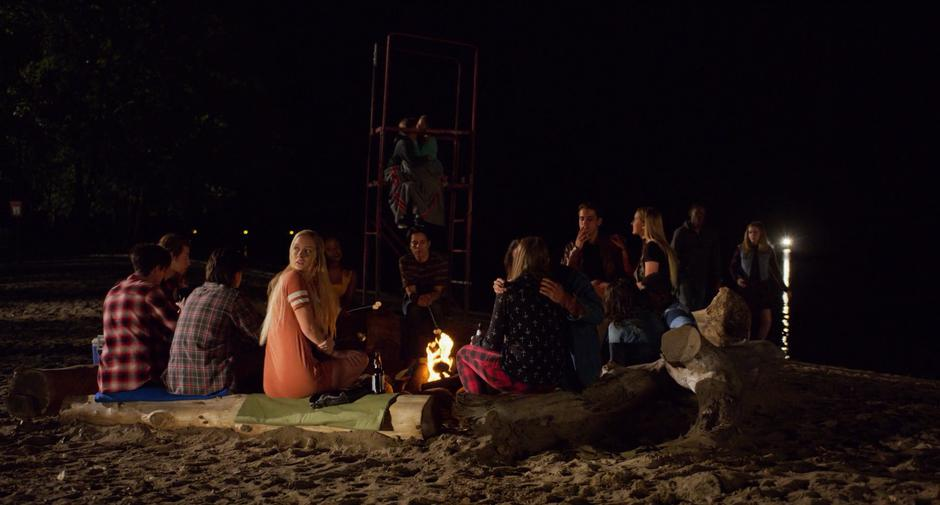 Hope turns around from the party of kids around the campfire when she hears a car speeding down the beach.