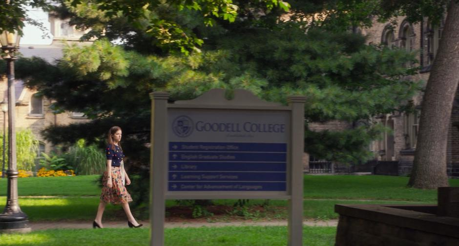 Stephanie walks across campus past the Goodell College sign.