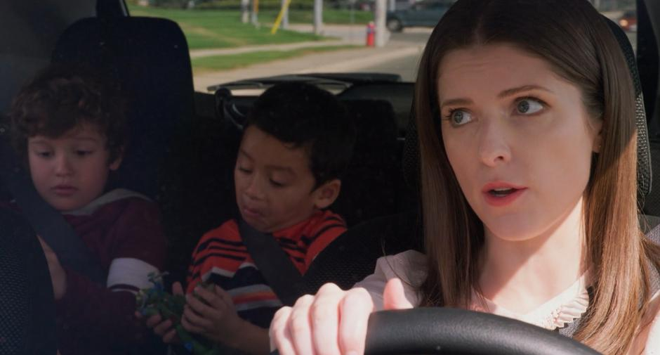 Stephanie tells Miles and Nicky to put away their dolls as she drives them across town.