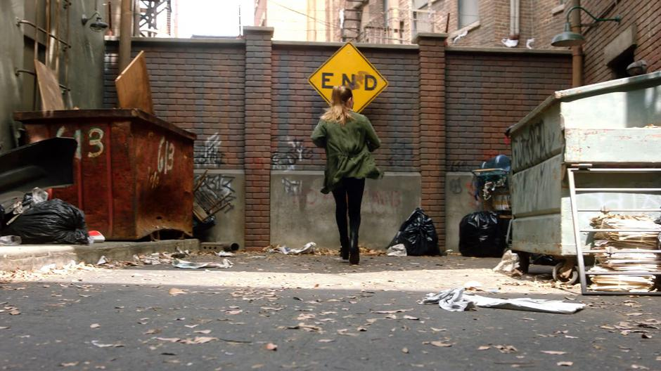 Chloe comes to a stop when she finds the alley blocked in a dead end.