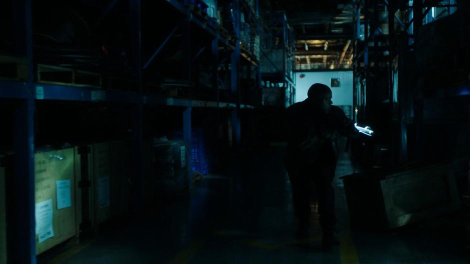 One of the gun smugglers searches the dark warehouse for the attacker.