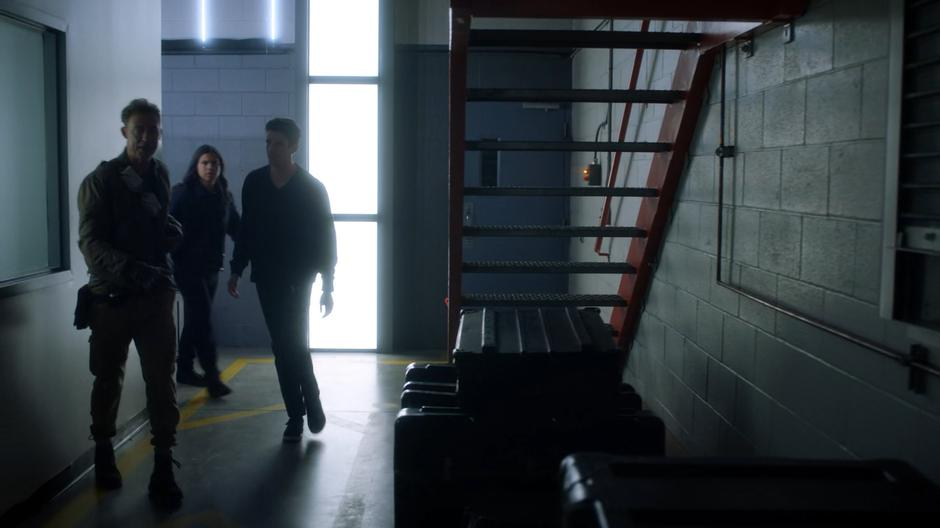 Nash leads Cisco and Barry around the corner through the lab.