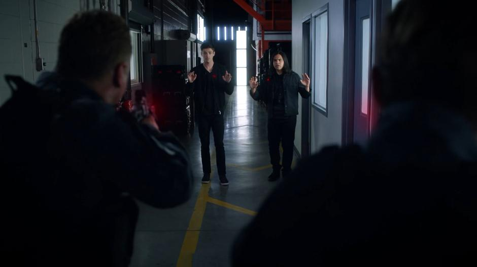Two guards hold Barry and Cisco at gunpoint.