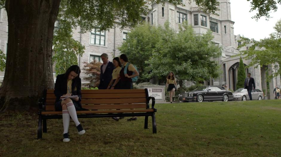 Young Lena sits alone doing homework on a bench in front of the school as Andrea approaches from the distance.