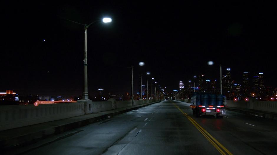 The truck carrying the chemical barrels drives across the bridge at night.