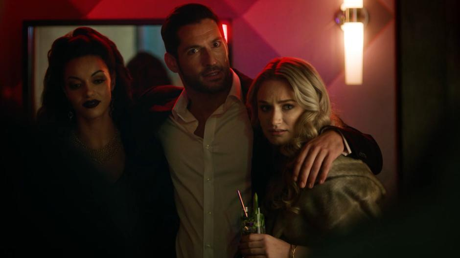 Lucifer opens the back door of his club with his arms around two women and sees Constantine standing outside.