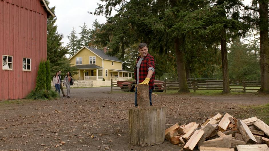 Lois, Clark, and Iris come around the corner of the barn to see Earth-167 Clark chopping wood.