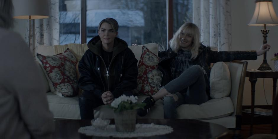 Kate sits on the couch next to Alice who is spreading her arms wide and smiling at Tammy.
