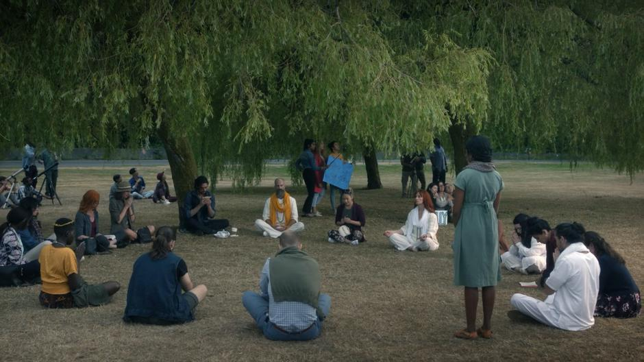 Eliot sits against a tree eating his sandwich while people pray in the circle around him.
