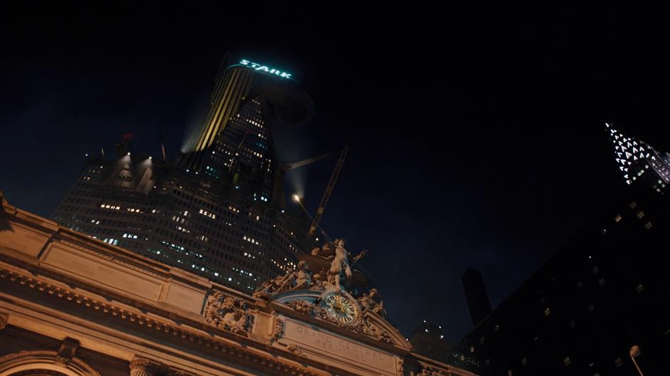 Iron Man flies over Grand Central Station up towards the under construction Stark Tower.