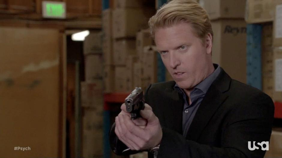 The FBI agent points his gun at Shawn and Gus.