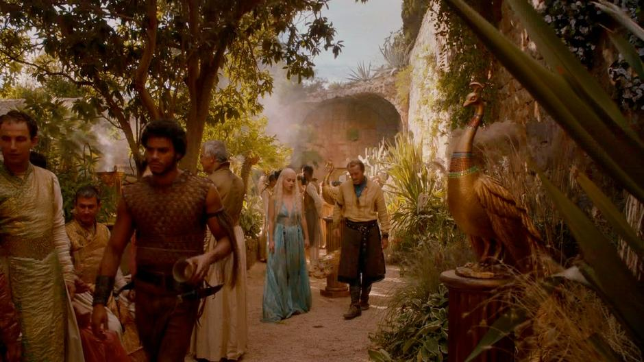 Daenerys and Bronn chat while walking through the party.