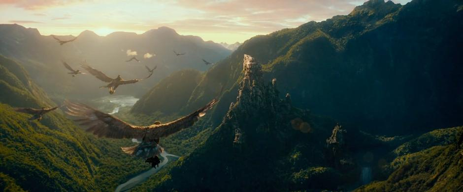 Eagles carrying Thorin's company fly down a valley toward the Carrock.