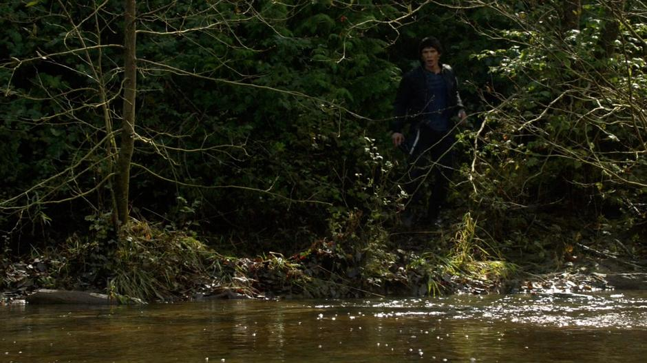 Bellamy walks down a path to the river with the radio.