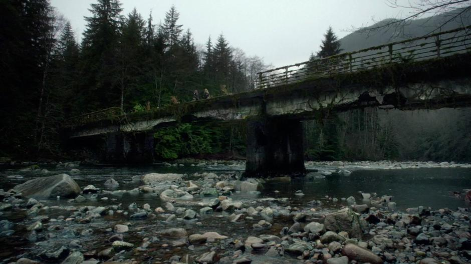 Clarke and Anya meet at the middle of a dilapidated bridge.