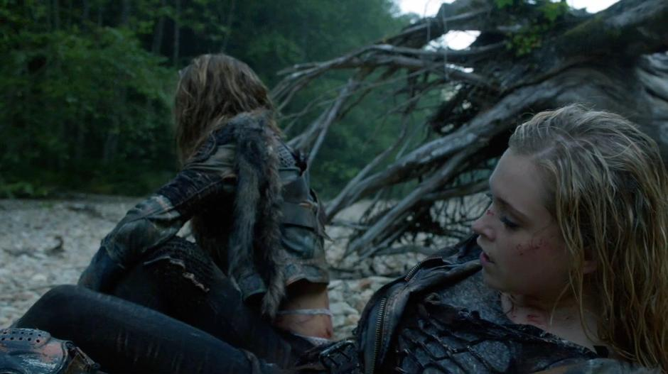 Clarke sits up while Anya looks for a rock to smack her with.