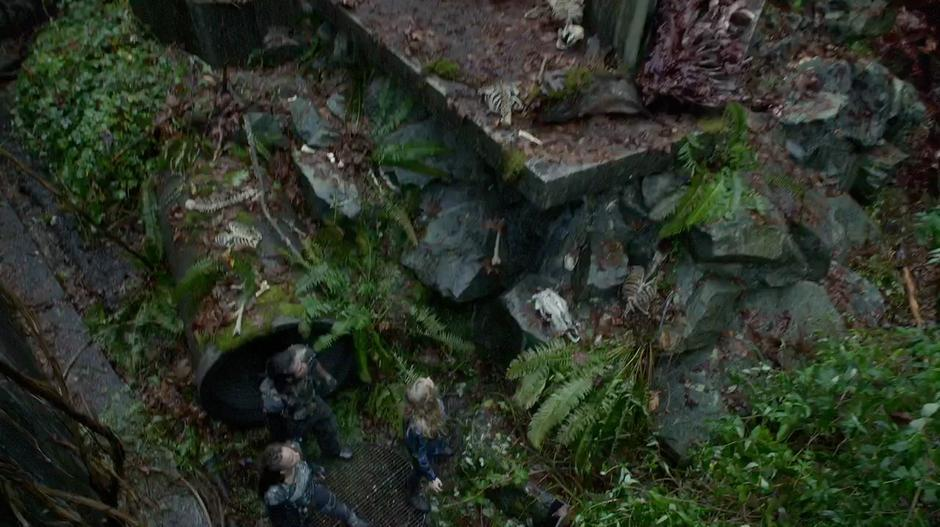 Clarke, Lexa, and the other Grounder look around the enclosure.