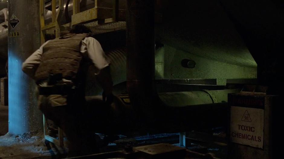 Bellamy crouches underneath the tank to get a better look at the gauge.
